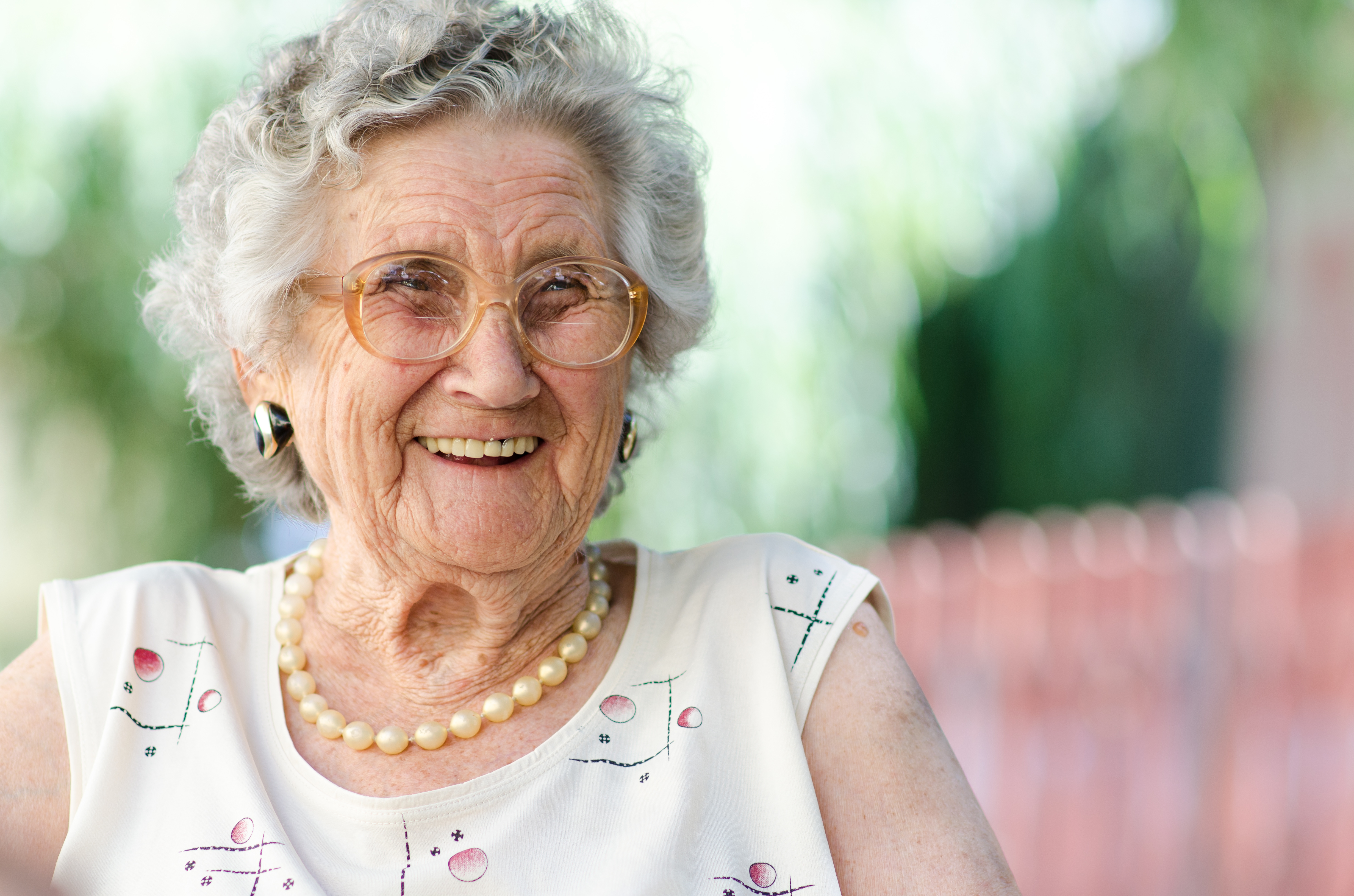 Older white woman wearing glasses and smiling