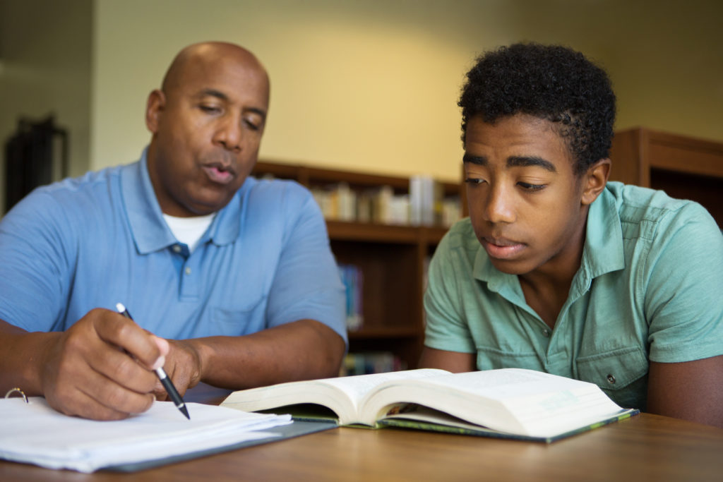 Adult male helping young adult with paperwork