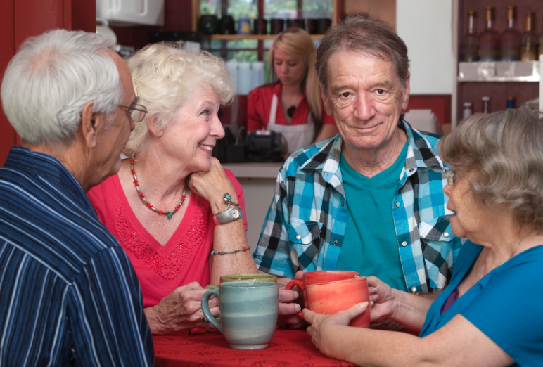 A group of older adults chatting and drinking coffee